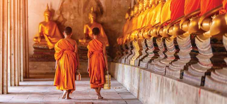Two young Buddhists walking past row of gold Buddha statues