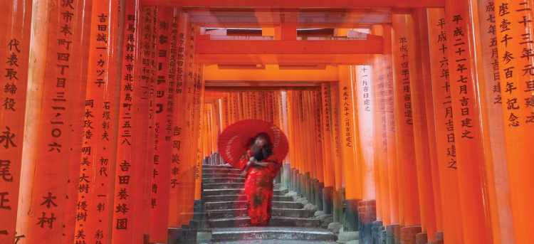 Woman walking with red umbrella through Torii Gate tunnels