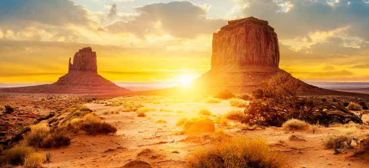 Golden sunlight over rock formations in Monument Valley