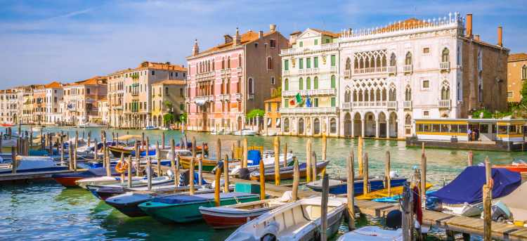 Row of gondolas moored on Venice canal | Riviera Travel | yacht cruise