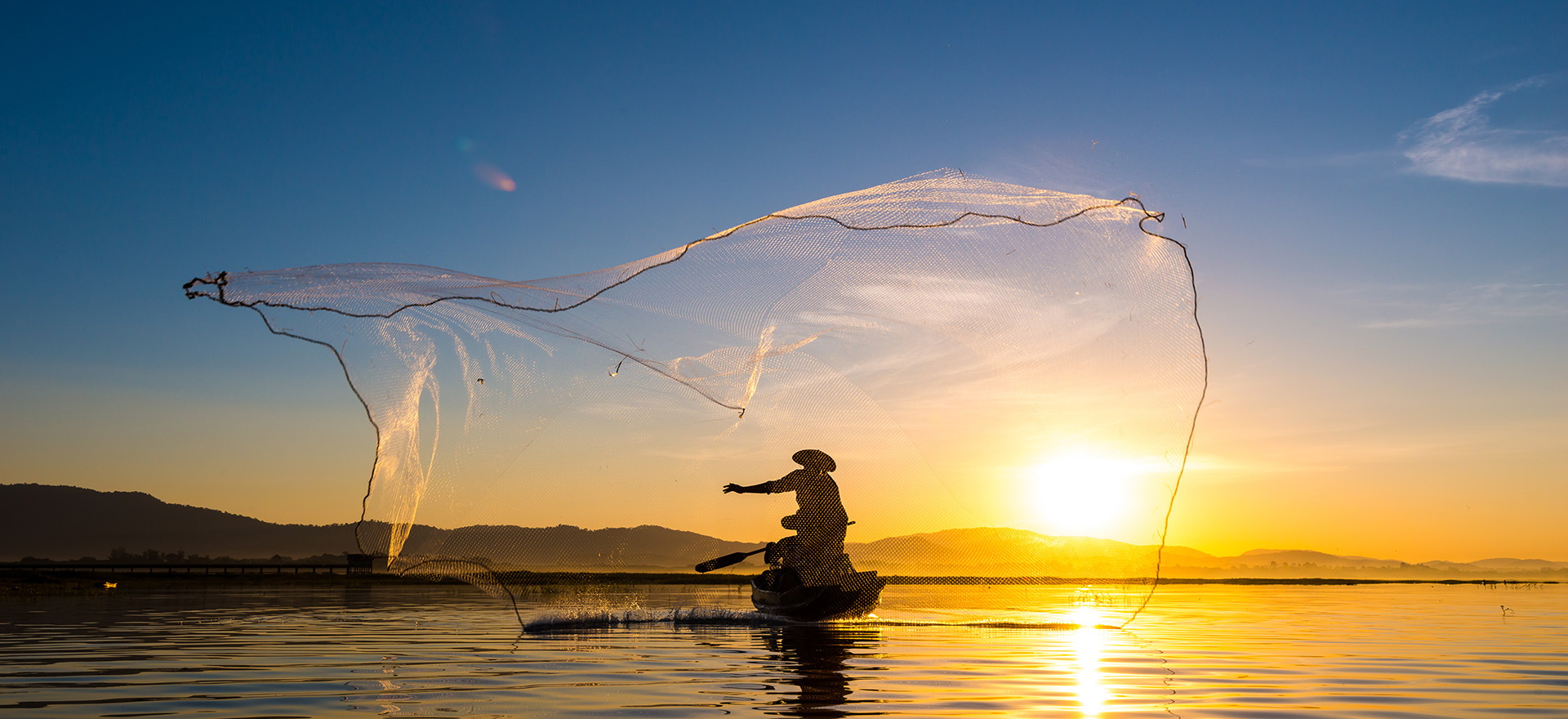 Fisherman with large fishing net on river