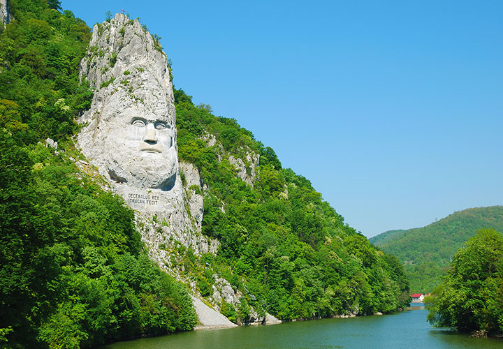 Huge grey rock sculpture of Decebalus built into green hillside over the Danube river