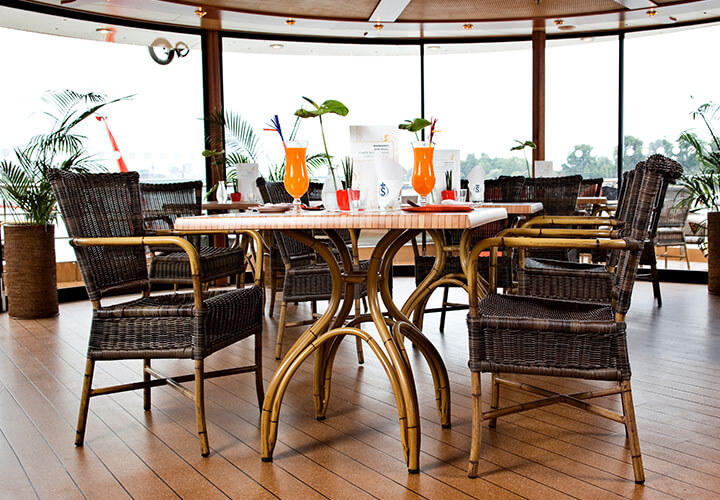 Bistro dining table with chairs and orange cocktails before panoramic windows