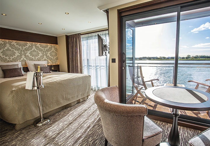 Deluxe balcony suite with double bed, indoor and outdoor seating and floor to ceiling windows